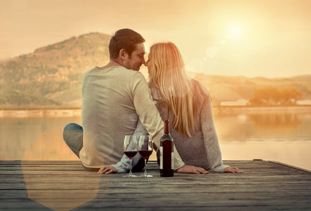 Romantic Couple sitting on the pier with red wine. Banque d'images