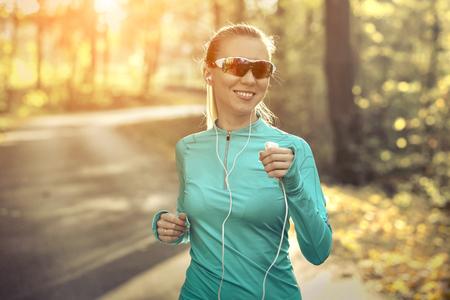 Runner in action at autumn under sunlight. Standard-Bild