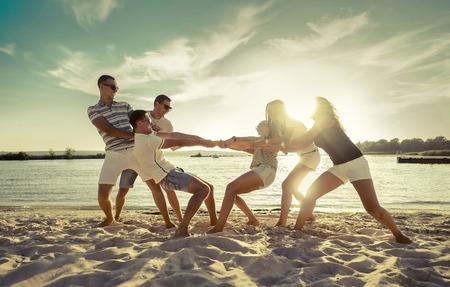 Friends funny tug of war on the beach under sunset sunlight. Reklamní fotografie - 49937707