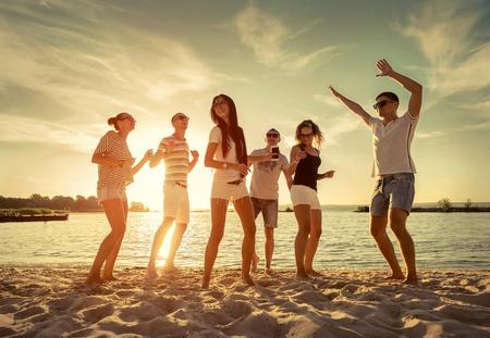 baile: Amigos de baile divertido en la playa bajo la luz del sol puesta de sol. Foto de archivo
