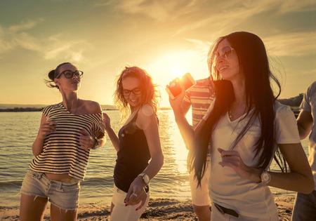 sunset: Friends funny dance on the beach under sunset sunlight.