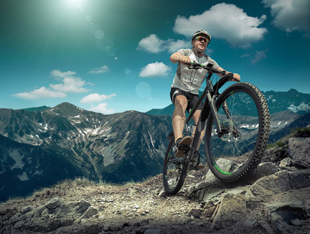 mountain bicycle: Man in helmet and glasses stay on the bicycle under sky with clouds.