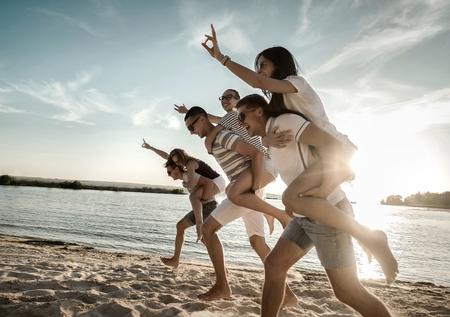 freiheit: Freunden Spaß am Strand unter Sonnenuntergang Sonnenlicht.