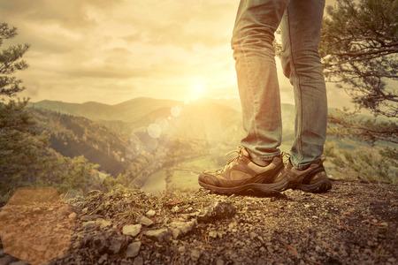 footwear: Men stay in Mountains footwear on the beautiful view.