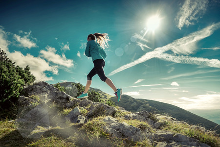 Female running in mountains under sunlight. Banque d'images