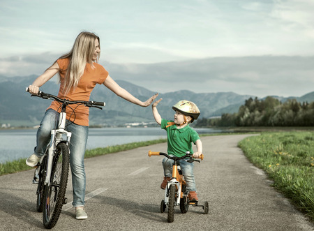 recreational: Happiness Mother and son on the bicycles funning outdoor Stock Photo
