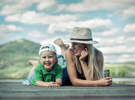 dia soleado: Madre Felicidad e hijo en el muelle en d�a soleado bajo la luz solar.