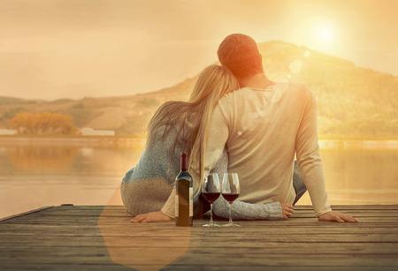 Romantische Paar sitzt auf dem Pier mit Rotwein.