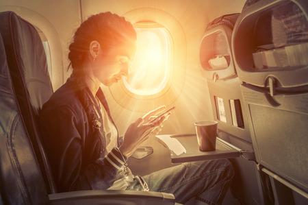 Mujer sentada en avión y en busca de teléfono mobil. Foto de archivo