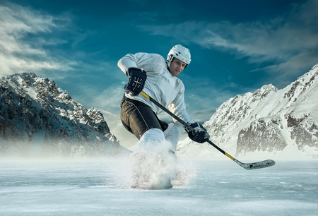 hockey: Ice hockey player in action outdoor around mountains