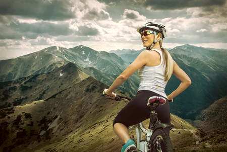 mountain sunset: Beautiful woman in helmet and glasses stay on the bicycle around mountains.