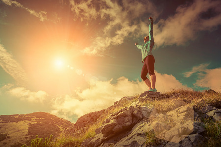 endurance: Female stay on the top of mountain under sunlight.