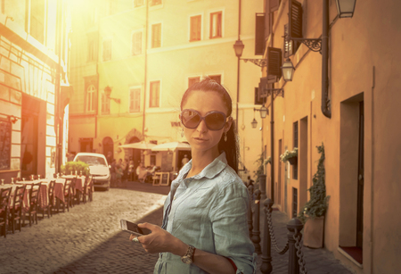 urban people: Female tourist shoot by phone on the Roman street.