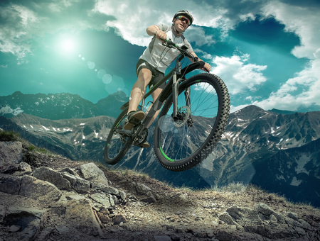 extreme: Man in helmet and glasses stay on the bicycle under sky with clouds.
