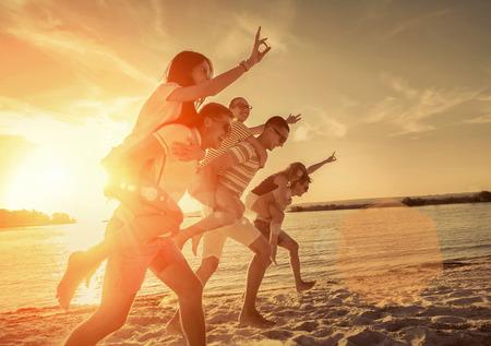 amistad: Amigos de la diversión en la playa bajo la luz del sol puesta de sol.