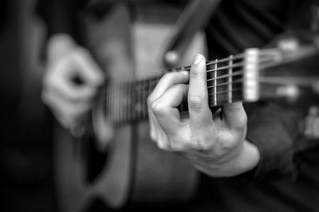 gitara: Młody mężczyzna gra na gitarze akustycznej