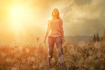 puesta de sol: Mujer de la felicidad permanecer al aire libre bajo la luz del sol de la puesta del sol
