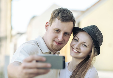 selfy: Touristic couple shooting on the modile phone selfy at the city streets under sunlight.