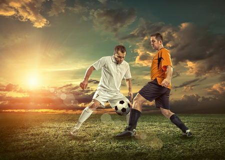 action sports: Soccer player with ball in action outdoors. Stock Photo