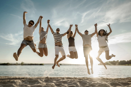 outdoor event: Friends jumping on the beach under sunset sunlight.