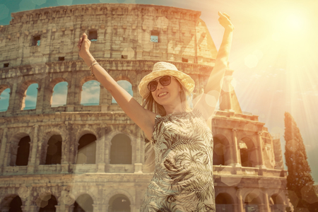 rome: Happiness Female tourist at white hat on the beautiful view of coliseum in Rome. Stock Photo