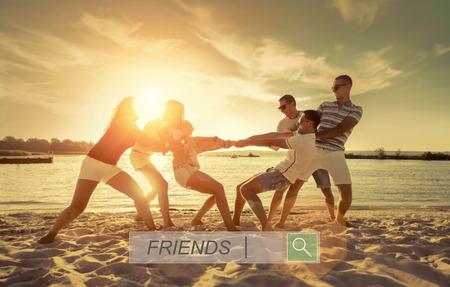 Friends funny tug of war on the beach under sunset sunlight. Imagens