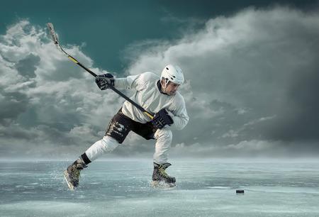 hockey sobre hielo: Jugador de hockey sobre hielo al aire libre en la acci�n alrededor de las monta�as