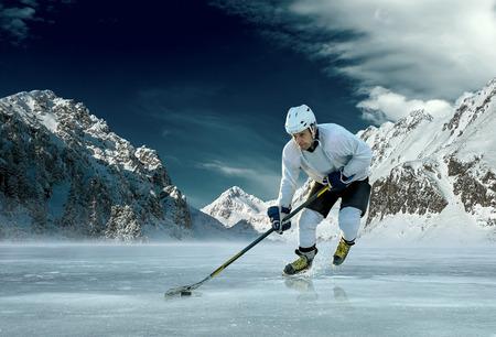 hockey sobre hielo: Jugador de hockey sobre hielo al aire libre en la acción alrededor de las montañas