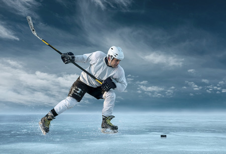 hockey stick: Ice hockey player in action outdoor around mountains