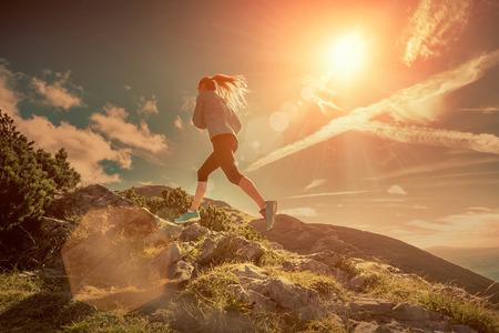 lifestyle: Mujer corriendo en montañas bajo la luz del sol. Foto de archivo