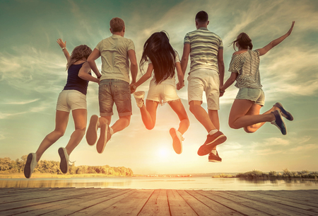 20 29: Group of friends jumping on the pier under sunlight.