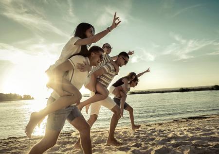 competencia: Amigos de la diversión en la playa bajo la luz del sol puesta de sol.