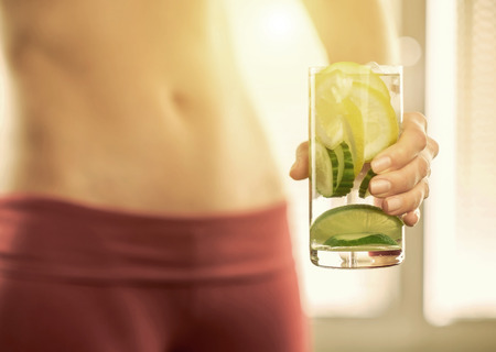 summer fruits: Healthy coctail in the hands of fitness female.