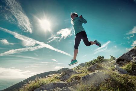 non urban: Female running in mountains under sunlight. Stock Photo