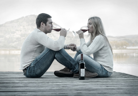 wine glasses: Romantic Couple sitting on the pier with red wine. Stock Photo