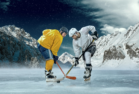 sportsmanship: Ice hockey player in action outdoor around mountains