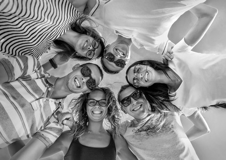 20 29: Group of friends on the beach under sunlight. Stock Photo