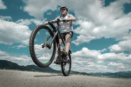 outdoor pursuit: Man in helmet and glasses stay on the bicycle under sky with clouds.