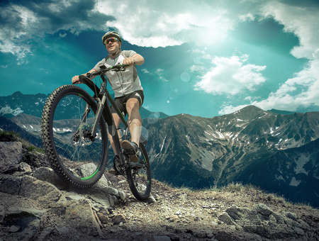 sun glasses: Man in helmet and glasses stay on the bicycle under sky with clouds.