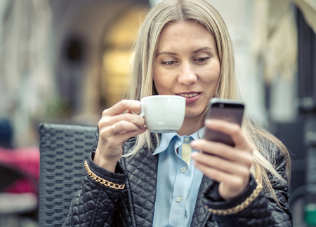 20 29: Woman seating in cafe with her phone and coffee.