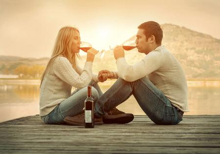 tomando vino: Pareja romántica, sentado en el muelle con el vino tinto. Foto de archivo