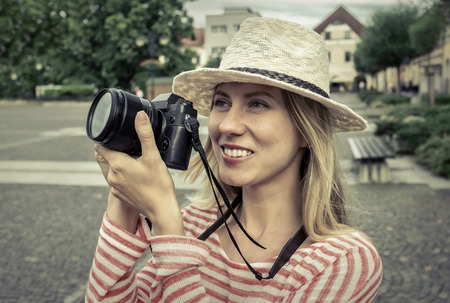 20 29: Woman with camera on the street.
