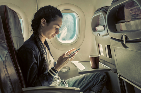 looking  up: Woman sitting at airplane and looking to mobil phone.
