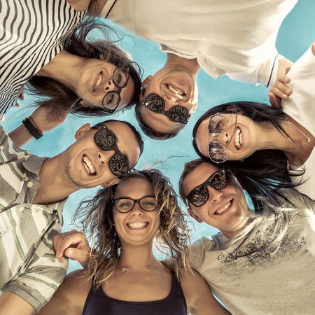 circle of friends: Group of friends on the beach under sunlight. Stock Photo