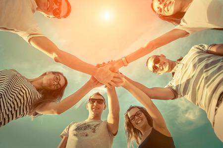 comunidad: Grupo de amigos en la playa bajo la luz solar. Foto de archivo