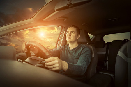 driving a car: Man sitting and driving in the car