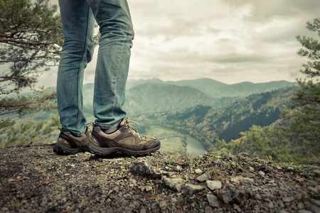 up view: Men stay in Mountains footwear on the beautiful view.