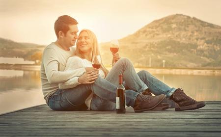 Casal romântico sentado no cais com vinho tinto.