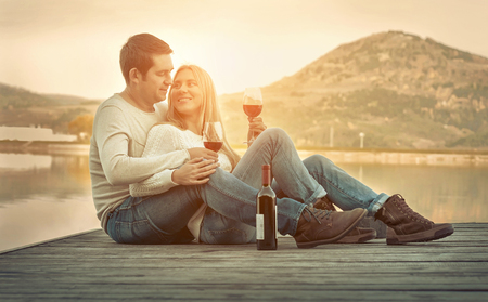 Romantic Couple sitting on the pier with red wine. Foto de archivo