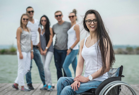 disabled: Young people on the pier with them disabled friend. Stock Photo